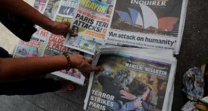 A woman sells newspapers with photos headlines of the Paris attacks in Manila on November 15, 2015. Photograph: Jay DIrecto/AFP/Getty Images