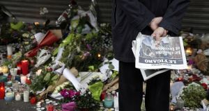 Flowers and candles are placed outside the Le Belle Equipe restaurant along the Rue de Charonne in central east Paris, on November 15th, 2015, two days after deadly attacks across the city. Photograph: Kenzo Tribouillard/AFP/Getty Images