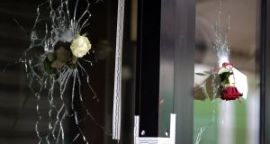 Roses are placed in bullet holes of the window of a Japanese restaurant along the Rue de Charonne in central east Paris, on Sunday, two days after deadly attacks across the city. Photograph:  Kenzo Tribouillard/AFP/Getty Images