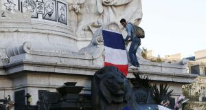 LA RÉPUBLIQUE: A man hangs a French national flag on the Monument a la Republique as people gather at the Place de la Republique in Paris, on November 15th. Photograph: Patrick Kovarik/AFP/Getty Images