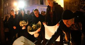 Members of U2 lay flowers on Saturday at a memorial site near the Bataclan concert hall in Paris. Photograph: Simon Dawson/Bloomberg