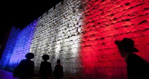 Ultra-orthodox Jewish men pass Jerusalem's Old City wall as it is illuminated yesterday with the colours of the French national flag in a gesture to show solidarity with the victims of the Paris attacks. Photograph: Lior Mizrahi/Getty Images