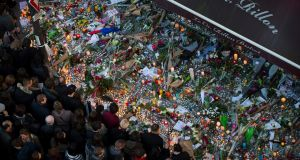 A crowd gathers to lay flowers and candles in front of the Carillon restaurant in Paris. Photograph: Ian Langsdon/EPA
