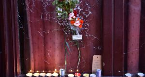 Candles  next to a flower in  a broken window of Le Carillon restaurant in Paris,  the site of one of the attacks in the French capital on Friday. Photograph: Loic Venance/AFP/Getty Images