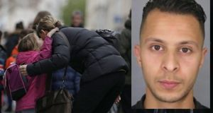 A child kisses a relative before going to school early on Monday 2015 in Paris, three days after the terrorist attacks that left over 129 dead and more than 350 injured. Police are searching for Salah Abdeslam (inset, a suspect in the attacks. Photograph: Kenzo Tribouillard/AFP/Getty Images