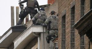 Belgian special forces police climb high on an apartment block during a raid, in search of suspected muslim fundamentalists linked to the deadly attacks in Paris in the Brussels suburb of Molenbeek on Monday. Photograph: Yves Herman/Reuters