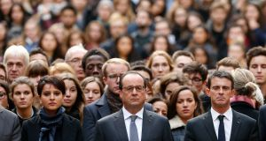 French president Francois Hollande, centre, flanked by French prime minister Manuel Valls, right, and French education minister Najat Vallaud-Belkacem, center left, stands among students during a minute of silence in the courtyard of the Sorbonne University in Paris. Photograph: Guillaume Horcajuelo/Pool via AP