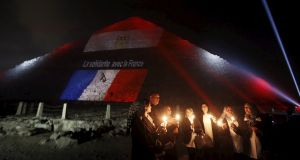 "Egyptians light candles as the French and Egyptian flags and France's national colours are projected onto one of the pyramids at Giza, outside Cairo,   in tribute to the victims of the Paris attacks. The words on the pyramid read: ""Solidarity with France"". Photograph:  Amr Abdallah Dalsh/Reuters"