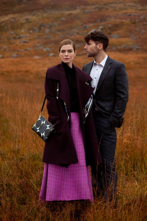Nikki wears burgundy oversized collar coat, €425, Peter O'Brien, black turtle neck, €195, pink full skirt, €295, both Niamh O'Neill; printed scarf, €125 Susannagh Grogan; geometric print handbag,€185, Orla Kiely.  Sam wears check blazer, €210, Remus; shirt €79, Brent Pope; charcoal trousers, €70, Remus.