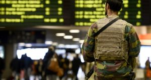 A military police soldier patrols the Brussels Midi train station  in Brussels. Belgium's national security level has been raised to three following the terrorist attacks on Paris. Photograph: Dirk Waem/AFP/Getty Images