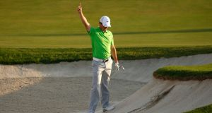 Rory McIlroy celebrates after he holed out from the bunker at the 18th hole during the first round of the DP World Tour Championship in Dubai. Photo: Paul Childs/Reuters