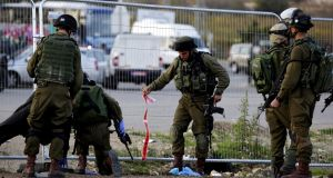 Israeli soldiers investigate  the scene of  a fatal stabbing of an Israeli woman at a bus stop and hitch hiking post outside Efrat in the West Bank settlement block of Gush Etzion, south of Jerusalem,  November 22nd, 2015. Photograph: Jim Hollander/EPA