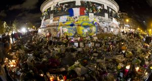 It is possible to love a place the way one loves a person, and everyone loves Paris: tributes at the base of the Monument a la Republique at the Place de la Republique square. Photograph: Joel Saget/AFP/Getty Images