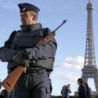 A French police officer stands guard by the Eiffel tower. Photograph: Eric Gaillard/Reuters