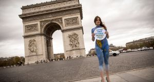 """We need a political breakthrough in Paris to begin addressing this injustice."" A model from PETA (People for the Ethical Treatment of Animals) with a world map painted on her body poses in front of the Arc de Triomphe in Paris in the run up to COP21"