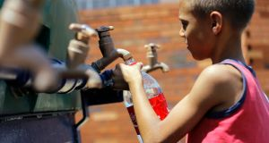 A young boy fills his cup from a water tanker in Coronation, Johannesburg, as South Africa experiences its worst drought in decades. EPA/KIM LUDBROOK