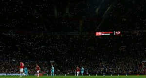 Manchester United fans wave their mobile phone lights during the seventh minute of the match in honour of former player George Best. Photograph: Phil Noble/Reuters/Livepic