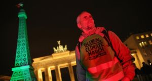 An activist stands next to an effigy of the Eiffel Tower bathed in green light in front of the Brandenburg Gate ahead of climate change marches scheduled for this weekend  in Berlin. Photograph: Sean Gallup/Getty Images