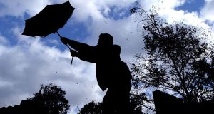 A walker struggling with his umbrella in gusts of strong wind. Photograph: Kirsty Wigglesworth/PA Wire