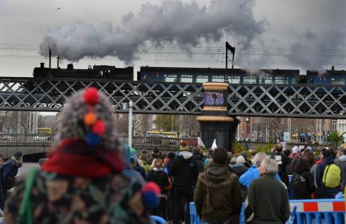 Protesters watch as a steam train crosses Butt Bridge at the start of the climate change protest in Dublin. Photograph: Cyril Byrne/The Irish Times