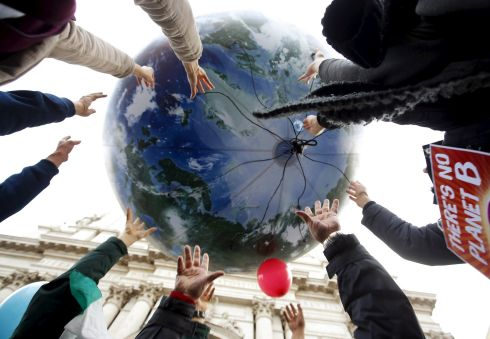 Protesters throw up a globe-shaped balloon during a climate change rally in Rome. Photograph: Alessandro Bianchi/Reuters