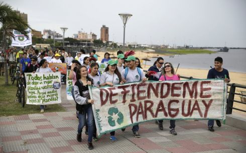 "PARAGUAY: Protesters hold placards and banners during a rally in Asuncion, Paraguay ahead of the 2015 Paris Climate Change Conference. The banner (front) reads, ""Defend Paraguay"". Photograph: Jorge Adorno/Reuters"