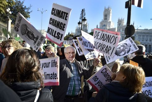 "A man distributes placards against climate change during the ""Global Climate March"" in Madrid. About 10,000 people marched through the city ahead of the summit in Paris. Photograph: Gerard Julien/AFP/Getty Images"