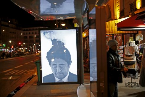 "PARIS: A poster by street artist Bill Posters, showing a satirical portrait of Japan's prime minister Shinzo Abe, as part of the ""Brandalism"" project is displayed at a bus stop in Paris. Photograph: Benoit Tessier/Reuters"