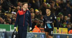 An injured Alexis Sanchez of Arsenal leaves the pitch at Carrow Road. Photograph: Michael Regan/Getty Images)