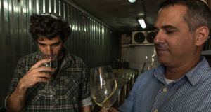 Yaakov Henig, a graduate student at Ariel University, and Eliyashiv Drori, an oenologist at the university, taste wine made from local grapes at the university in the occupied West Bank. Photograph: Rina Castelnuovo/The New York Times