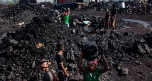 Day labourers load coal into trucks at an open pit coal mine in the Bestacolla Colliery in Jharia, India. Photographer: Sanjit Das/Getty Images