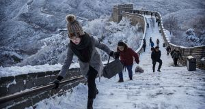 Chinese tourists walk on a slippery section of ice as snow is seen on the Great Wall after a snowfall on November 23, 2015 near Beijing, China. Photograph: Kevin Frayer/Getty Images)