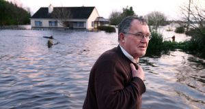 Tom Quinn with his flooded house in the backround at the townland of Caherfurvaus near Craughwell. Photograph: Joe O'Shaughnessy