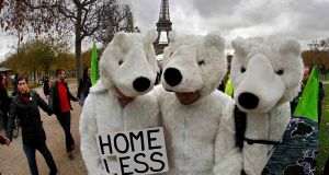 Three environmentalists wear polar bear costumes as they take part in a demonstration near the Eiffel Tower in Paris, France, as the World Climate Change Conference 2015 (COP21) on Saturday.  Photograph: Reuters