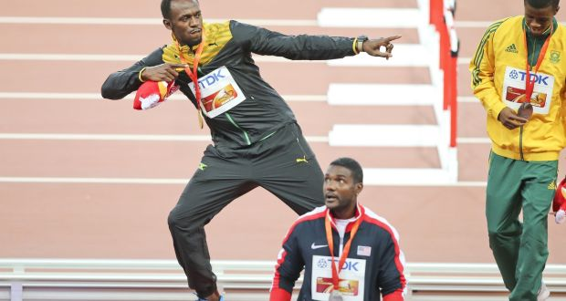 969830e9dbe4e8 Usain Bolt performs his signature pose with his gold medal after beating  Justin Gatlin at the