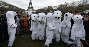 Costumed activists demonstrate near the Eiffel Tower, in Paris,  during the COP21  United Nations Climate Change Conference. Participating nations agreed to keep global temperature rises below 2 degrees. (AP Photo/Matt Dunham)