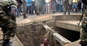 A man begs for help from the military as he stands in a drain where he had hid himself to escape a lynching by a mob at the Cibitoke district of Burundi capital, Bujumbura last May 7, 2015. Photograph: Aymeric Vincenot/AFP/Getty