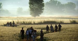 Migrants walking through a field to cross the border from Greece to Macedonia near the Greek village of Idomeni on August 29th. Photograph:   Aris Messinis/AFP/Getty Images