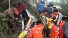 Thai rescue workers remove bodies and injured Malaysian passengers from the wreckage of a tourist bus after it crashed on a mountain roadside in the Doi Saket district in northern Thailand. Photograph: EPA