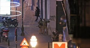 Armed special forces of the police are pictured during searchings in the Rue Antoine Dansaert street in central  Brussels on Sunday night. Photograph: Nicholas Maeterlinck/Belga/AFP/Getty Images.