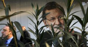 People walk past a picture of Spain's acting prime minister Mariano Rajoy outside the People's Party (PP) headquarters in Madrid