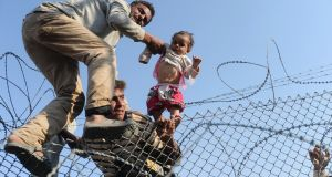 A Syrian child is lifted over a border fence into Turkish territory in June. Photograph: Bulent Kilic/AFP/Getty