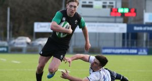 Ireland U-20's Terry Kennedy runs in for a try despite the efforts of Leinster's Tim Foley at Donnybrook Stadium. Photograph: Cathal Noonan/Inpho