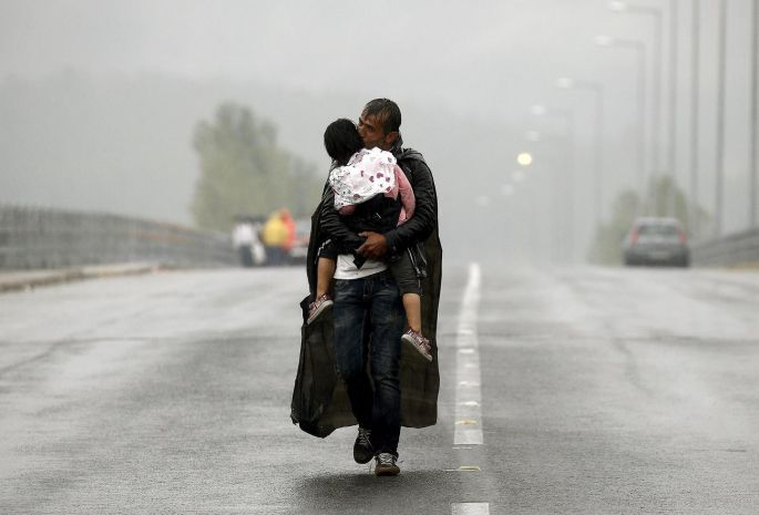 A Syrian refugee kisses his daughter as he walks through a rainstorm towards Greece's border with Macedonia, near the Greek village of Idomeni in September. Photograph: Yannis Behrakis/Reuters