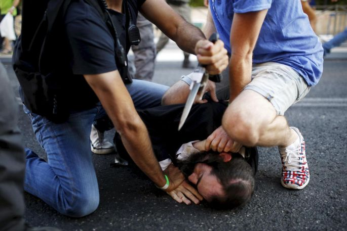 People disarm Yishai Schlissel, an Orthodox Jewish assailant shortly after he stabbed participants at the annual Gay Pride parade in Jerusalem on July 30th. Shira Banki (16) later died from her wounds. Schlissel had been released from prison following a similar attack on the 2005 parade. Photograph by Amir Cohen/Reuters.