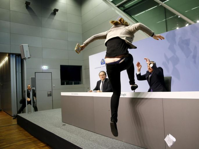 A protester jumps on the table in front of the European Central Bank president Mario Draghi during a news conference in Frankfurt, Germany in April. Photograph: Kai Pfaffenbach/Reuters.