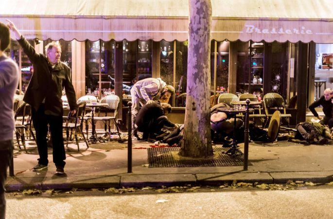 People lie on the pavement outside the Cafe Bonne Biere in Paris. The series of coordinated attacks left Paris reeling, and Belgian capital Brussels went into lockdown for five days. Photograph: Anthony Dorfmann AFP/Getty Images