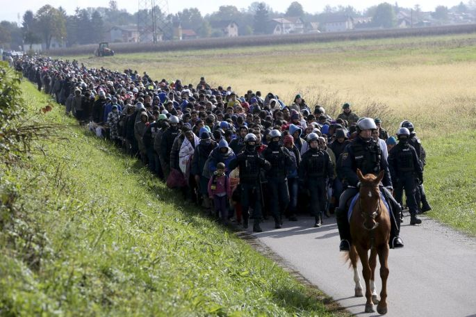 A mounted policeman leads a group of migrants near Dobova, Slovenia in October. Photograph: Srdjan Zivulovic/Reuters