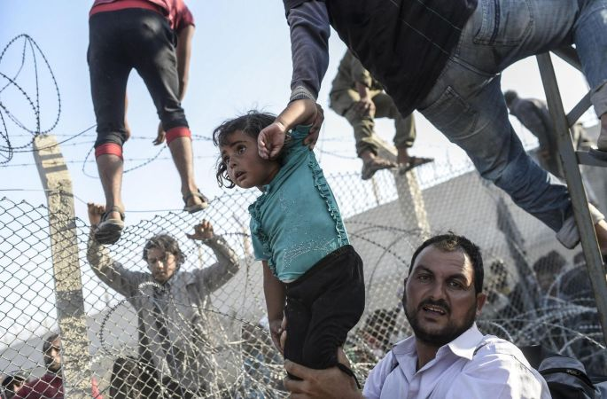 A Syrian child fleeing the war is lifted over border fences to enter Turkish territory illegally, near the border crossing at Akcakale in June. By that time, Turkey had taken in 1.8 million Syrian refugees since the conflict had erupted in 2011. Photograph: Bulent Kilic/AFP/Getty Images