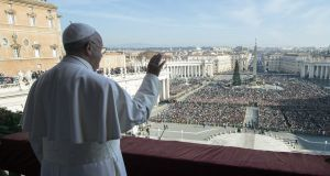 "Pope Francis standing on a balcony of St Peter's basilica during the traditional ""Urbi et Orbi"" Christmas message to the city and the world. Photograph: Osservatore Romano/AFP/Getty Images"